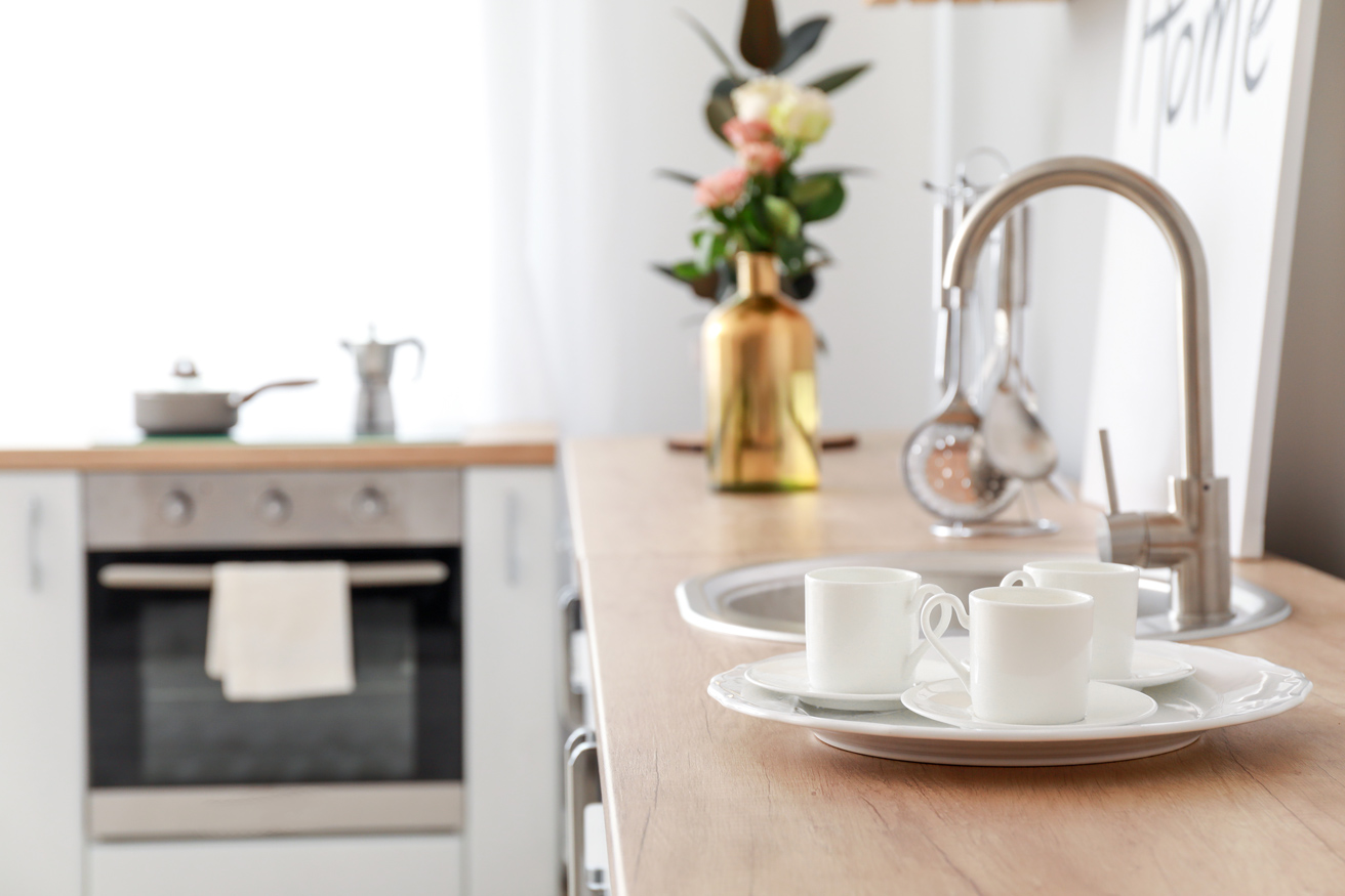 Close up image of kitchen tap with plates and cups on the area
